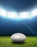 Rugby Stadium And Ball. A rugby stadium with a generic white rugby ball on a marked green grass pitch at night under illuminated floodlights Stock Photography