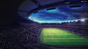 Rugby stadium with fans under roof with spotlights Stock Photos