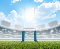 Rugby Stadium And Posts. A rugby stadium with rugby posts on a marked green grass pitch in the daytime under a blue sky Stock Photos