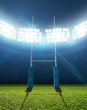 Rugby Stadium And Posts. A rugby stadium with rugby posts on a marked green grass pitch at night under illuminated floodlights Stock Photo