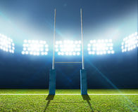 Rugby Stadium And Posts. A rugby stadium with rugby posts on a marked green grass pitch at night under illuminated floodlights Stock Photos