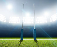 Rugby Stadium And Posts. A rugby stadium with rugby posts on a marked green grass pitch at night under illuminated floodlights Royalty Free Stock Photo