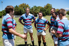 Rugby team discussing while standing at playing field. On sunny day Royalty Free Stock Photos