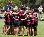 Rugby team talk. Team of young rugby players having a team talk with their coach Stock Photo