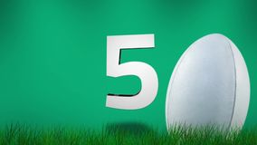 Rugbybal op gras met aftelprocedure tegen groene achtergrond stock video