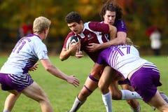 Rugbyspelaren övermannas av hans motståndare Arkivfoto