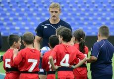 Rugbyspeler met jonge geitjes stock foto