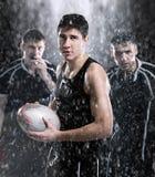 Rugbyspieler im Regen Stockfotos
