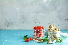 Rugge av shimejichampinjonen och k?rsb?rsr?da tomater i krus royaltyfri fotografi