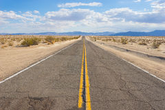 Rugged Asphalt Desert Road. Rugged stretch of roadway in Mojave Desert of American southwest royalty free stock image