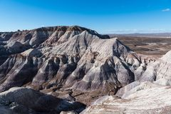 Rugged, barren, and heavily eroded desert mountain peaks in Petrified Forest National Park, Arizona. Rugged, barren desert landscape of sharp peaks and valleys stock photography