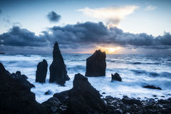 Rugged beach in Iceland. A remote beach in Iceland shows sharp rocky reefs protruding 20 feet out of the shallow water during a sunset royalty free stock photography