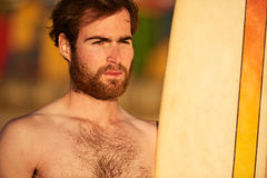 Rugged bearded male surfer portrait next to surf board Royalty Free Stock Photography