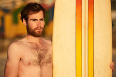 Rugged bearded male surfer portrait next to surf board Royalty Free Stock Photos