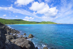 Rugged Caribbean coastline and rolling green hills. Rugged dark boulders contrast wide sandy beach and rolling green hills of Resaca Beach on the Caribbean stock image