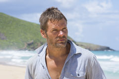 Rugged castaway man on deserted island. Closeup portrait of rugged unshaven Caucasian male castaway looking away from camera on sunny deserted island beach Royalty Free Stock Photos