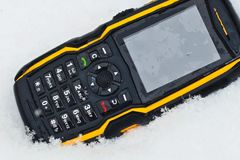 Rugged Cellphone in snow. Water resistant and rugged cellular telephone thrown into snow. Phone for outdoor and adventure use royalty free stock photography