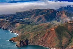 Rugged cliffs above Pacific Ocean by Point Bonita Lighthouse and fog rolling in Marin County California fly from San Francisco USA. Rugged coastal cliffs above stock images