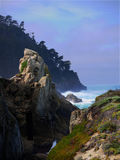 Rugged coast near Carmel California. Rugged coast line with steep hills at the Pacific Ocean close to Monterey California. Colorful clouds allowing a few rays of Stock Image