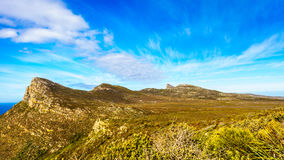 The rugged coast and wind swept peaks near Cape Point. On the Cape Peninsula in South Africa under blue sky Royalty Free Stock Images