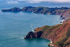 Rugged coastal cliffs above the Pacific Ocean by the Point Bonita Lighthouse in Marin County California fly from San Francisco USA. Rugged coastal cliffs above royalty free stock photography