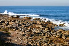 Jagged beach with rocks, white rushing crashing surging ocean waves and distant horizon. Rugged coastal landscape with stones. Rocky beachfront stock image