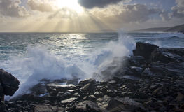 Rugged Coastline. The sun shines through the clouds while the rugged coastline takes a battering by a king wave stock image