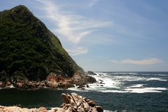 Rugged coastline. With tall mountain and green forest royalty free stock photos
