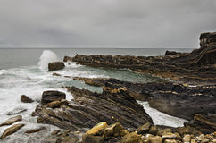 Rugged Coastline. The Atlantic Ocean meets Spanish coastline, far away a fisherman and some cormorants Stock Photo