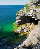 Rugged coastline with a cave. Large cave opening onto clear blue waters Stock Images