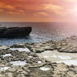 Rugged coastline of Gozo. Gozo is a small island of the Maltese archipelago in the Mediterranean Sea.  Rugged coastline delineated by sheer limestone cliffs, and Stock Photos