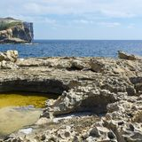 Rugged coastline of island of Gozo. Gozo is a small island of the Maltese archipelago in the Mediterranean Sea.  Rugged coastline delineated by sheer limestone Royalty Free Stock Image
