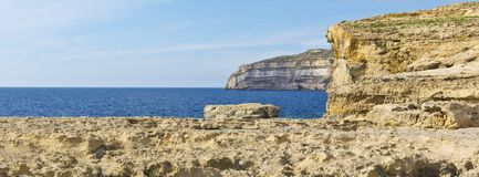 Rugged coastline of island of Gozo. Gozo is a small island of the Maltese archipelago in the Mediterranean Sea.  Rugged coastline delineated by sheer limestone Royalty Free Stock Photography