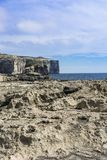 Rugged coastline of island of Gozo. Gozo is a small island of the Maltese archipelago in the Mediterranean Sea.  Rugged coastline delineated by sheer limestone Stock Photo