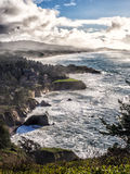 Rugged coastline with mist and clouds Royalty Free Stock Photography