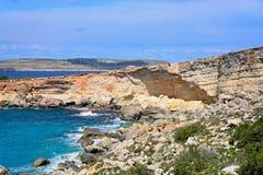 Rugged coastline at Paradise Bay, Malta. Rocky coastline with Comino to the rear, Paradise Bay, Malta, Europe Stock Image