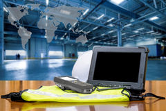 Rugged computers tablet and Bluetooth barcode scanner. In front of modern warehouse with world map. Logistics concept Stock Images
