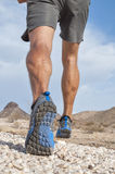 Rugged cross country runner. Closeup of male runner wearing rugged trail running shoes as he runs away from camera over rocky desert landscape Stock Photography