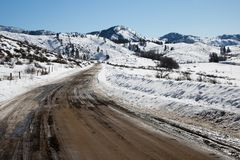 Rugged dirt road in winter with snow and mountains royalty free stock images