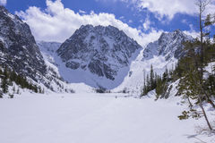 Rugged Dragontail Peak above frozen lake Royalty Free Stock Photography