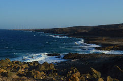 Rugged East Coast of Aruba with Wind farm in the Distance Stock Photography