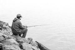 Rugged fisherman sitting on rocks on lake shore fishing. Black and white Stock Image