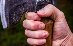 A rugged hand holding an axe ina firm grip. Closeup of a hand holding an axe in a firm grip. Symbolises determination, manliness, strength and vigor royalty free stock photo