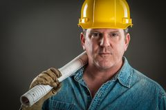 Rugged Handsome Contractor in Hard Hat Holding Floor Plans. Serious Contractor in Hard Hat Holding Floor Plans With Dramatic Lighting Royalty Free Stock Image