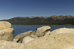 Rugged Lake Shoreline. A view of the mountains across Lake Tahoe on a rugged shoreline of boulders and rugged rocks on a clear sunny summer day Stock Photo
