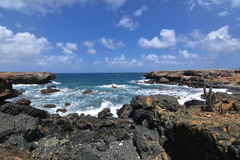 Rugged Lava Rocks Surrounding the Cove of Aruba`s Black Sand Bea Royalty Free Stock Images