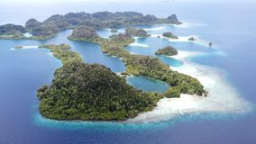 Aerial of Amazing Islands and Lagoon in Pef, Raja Ampat. Rugged limestone islands surround coral reefs and an idyllic, tropical lagoon in Pef, Raja Ampat stock video footage