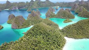 Aerial View of Tropical Islands in Wayag, Raja Ampat. Rugged limestone islands, surrounded by coral reefs, are found in an idyllic, tropical lagoon in Wayag stock video