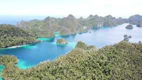 Aerial View of Islands in Wayag, Raja Ampat. Rugged limestone islands, surrounded by coral reefs, are found in an idyllic, tropical lagoon in Wayag, Raja Ampat stock footage