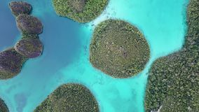 Aerial Footage of Islands and Colorful Lagoon in Raja Ampat. Rugged limestone islands, surrounded by coral reefs, are found in an idyllic, tropical lagoon in stock footage